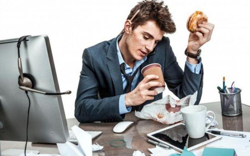 Homem comendo no escritório